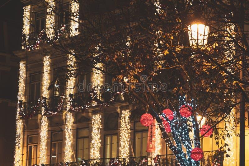 Bolas, luces del árbol y decoraciones rojas iluminadas del edificio de la Navidad en Lisboa, Portugal fotografía de archivo libre de regalías