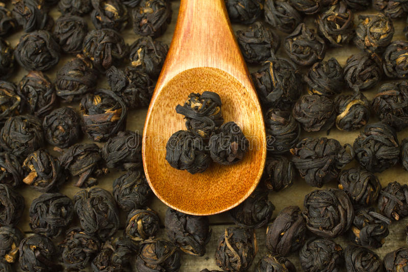 Bolas negras chinas de la hoja de té dentro de la cuchara de madera fotografía de archivo