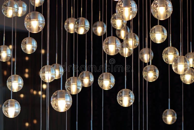 Bolas no candelabro na luz de lâmpada, ampolas que penduram do teto, lâmpadas da iluminação no fundo escuro, seletivo ilustração stock
