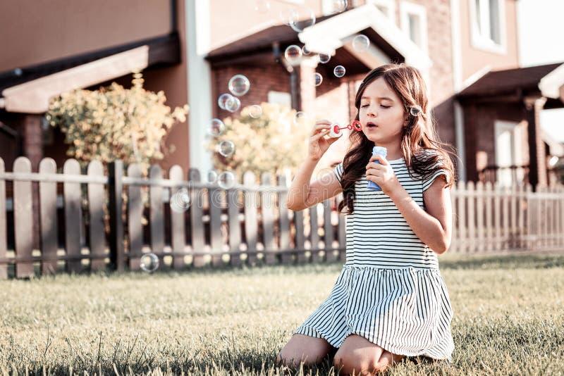 Bolas ocupadas del jabón de la muchacha que soplan bonita que se centran en el proceso imágenes de archivo libres de regalías