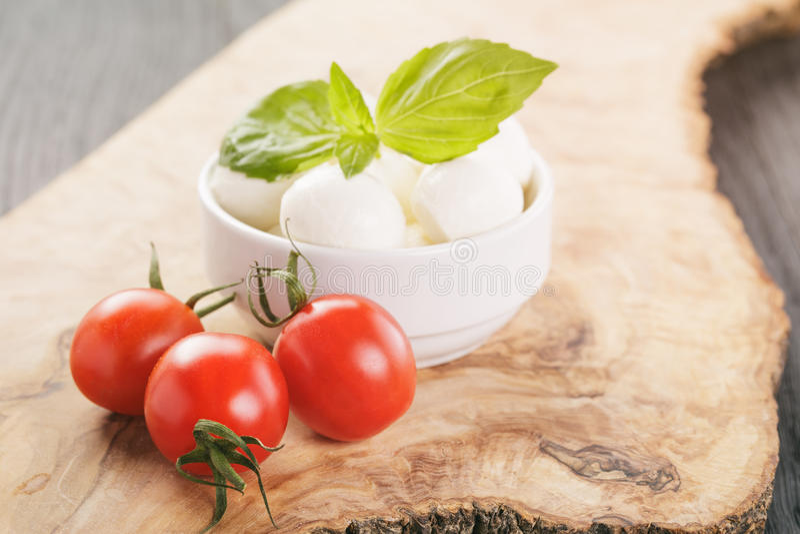 Bolas pequenas da mussarela na bacia branca com tomates de ameixa foto de stock royalty free
