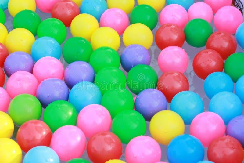 Bolas plásticas coloridas que flutuam na água imagem de stock royalty free
