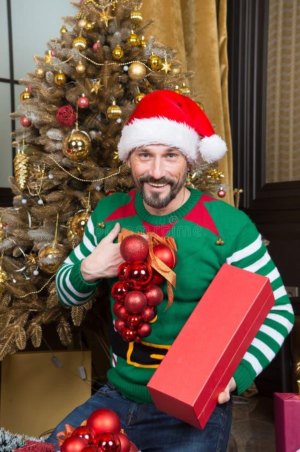 Bolas positivas do ornamento da terra arrendada do homem ao preparar-se para o Natal fotos de stock royalty free