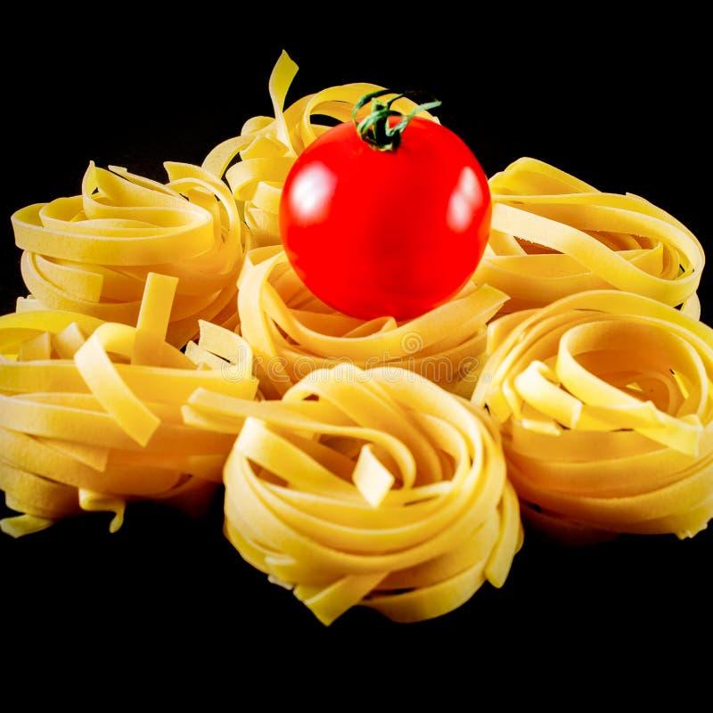 Bolas redondas da massa crua com o tomate no fundo preto Isolado fotos de stock royalty free