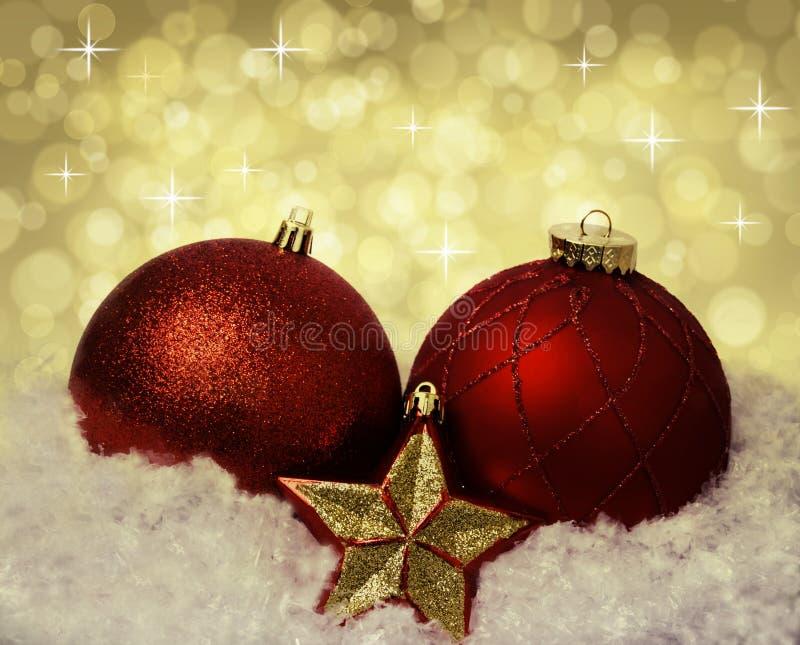 Bolas rojas de la decoración de la Navidad en la nieve imagenes de archivo