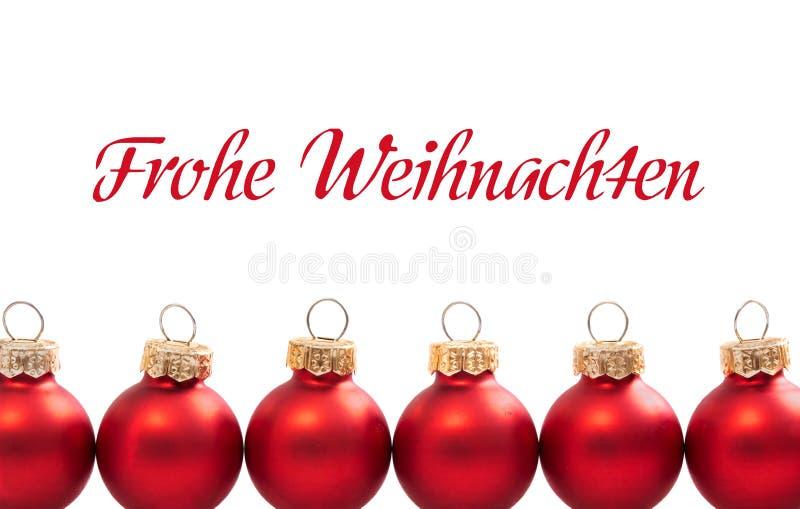 Bolas rojas de la Navidad con el texto alemán Frohe Weihnachten - en Feliz Navidad inglesa fotografía de archivo