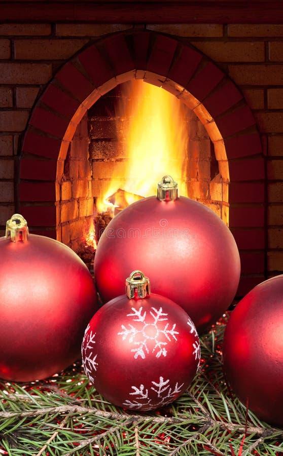 Bolas rojas de la Navidad en árbol y la chimenea spruce fotos de archivo libres de regalías