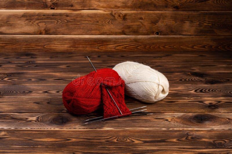 Bolas rojas y blancas del hilo y de agujas que hacen punto en un fondo de madera fotografía de archivo libre de regalías