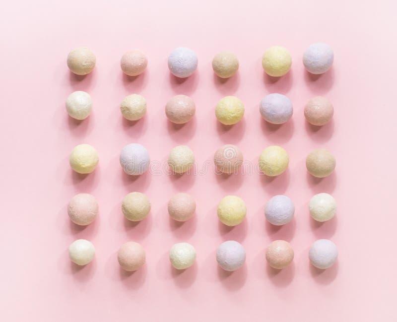 Bolas rosadas del colorete en fila en un fondo rosado foto de archivo
