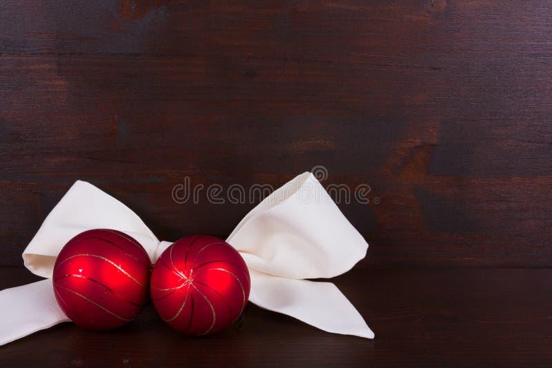 Bolas vermelhas do Natal com com a fita no fundo de madeira escuro fotos de stock royalty free