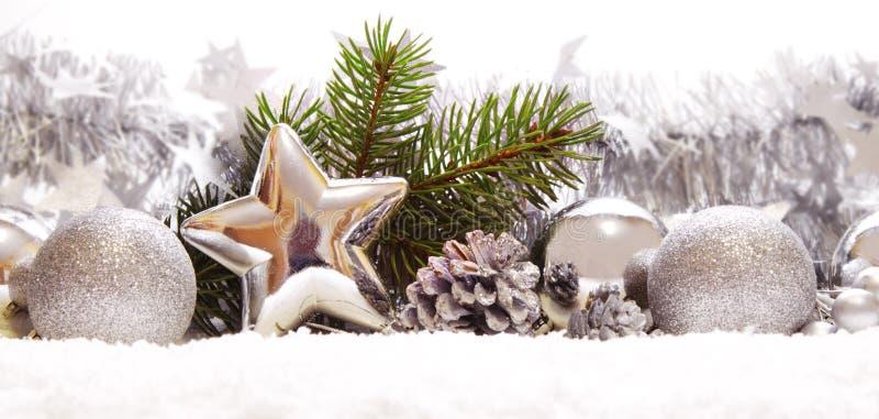 Bolas y decoración de plata de la Navidad en nieve foto de archivo