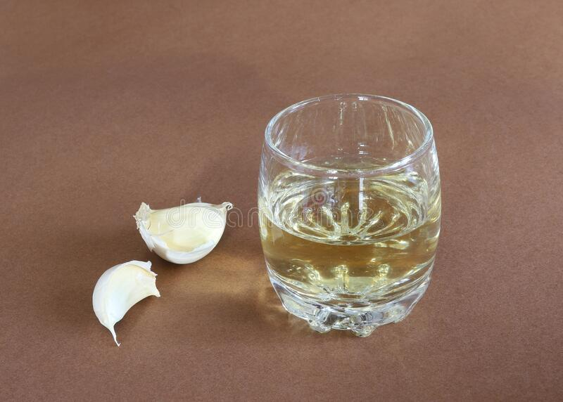 Bolbos de alho e cascos de alho com um copo de álcool raquia foto de stock royalty free