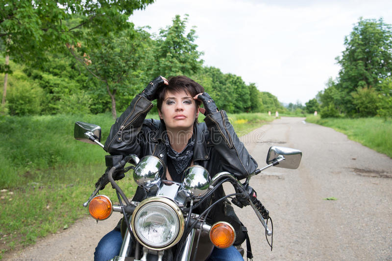 Bold and the beautiful girl on a bike royalty free stock photography