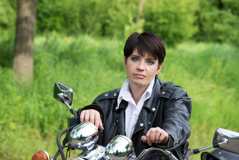 Bold and the beautiful girl on a bike royalty free stock photo