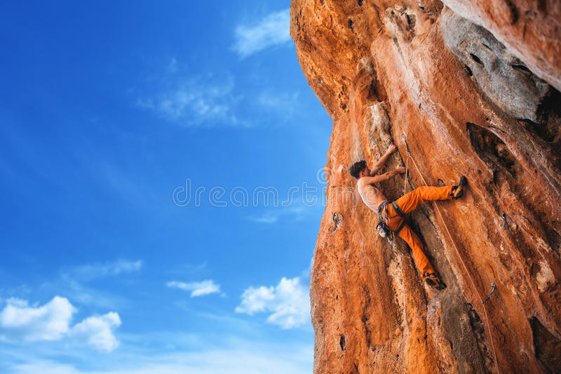 Bold choice - rock climbing. Rebellious rock climber on the wall - bold choice of real men. Stock Image stock photography