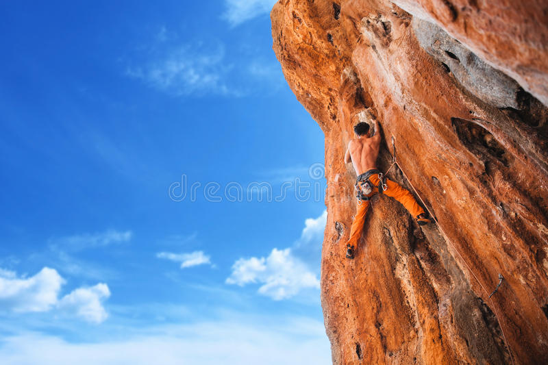 Bold choice - rock climbing. Rebellious rock climber on the wall - bold choice of real men. - Stock Image stock photo