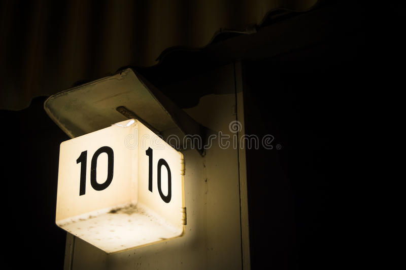 Bold number ten sign shining against large dark background stock images