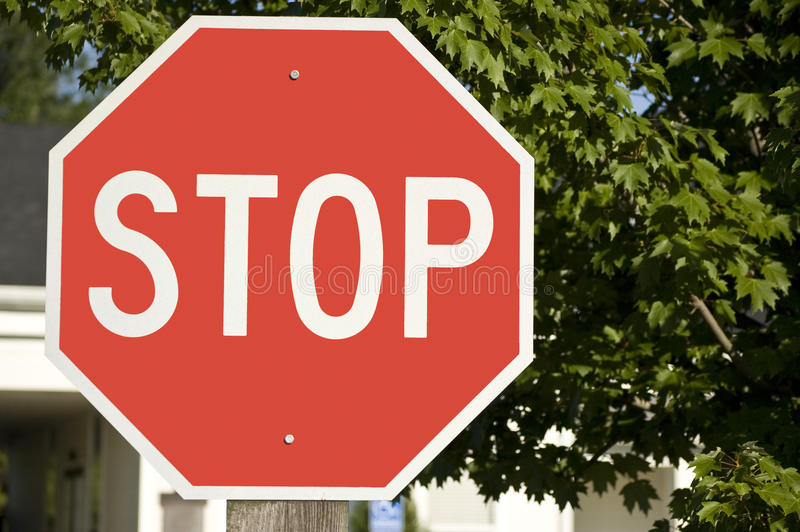 Bold Stop Sign. Close-up of a Stop Sign with trees behind stock photography