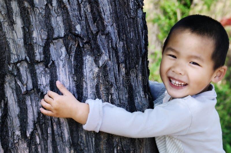 Bole dell'albero di abbraccio del ragazzo immagine stock libera da diritti