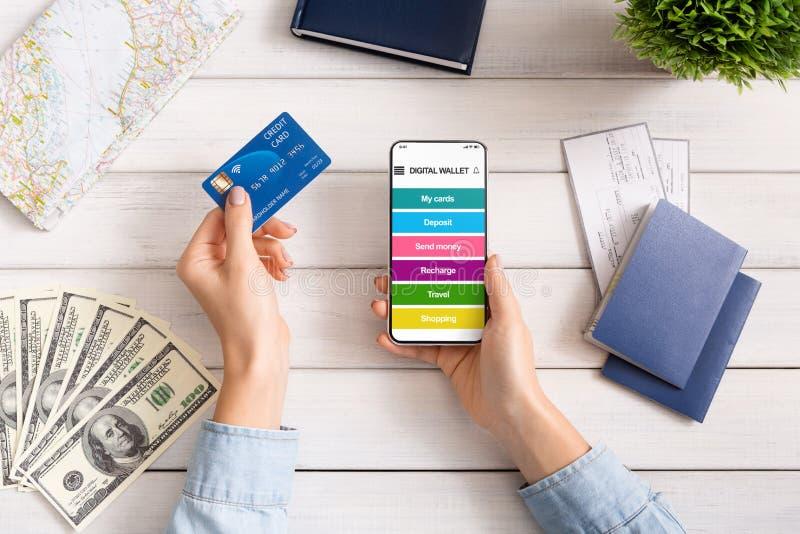 Boleto femenino de la reservación de la mano con el teléfono y la tarjeta de crédito imagenes de archivo
