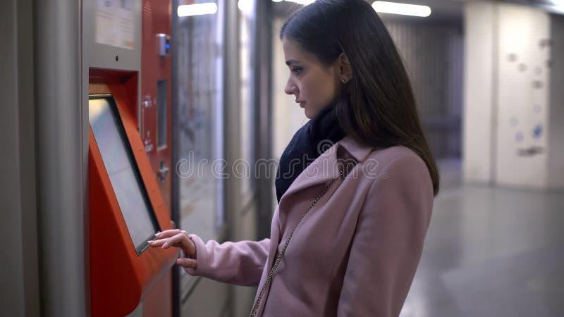 Boletos de compra del turista femenino joven en el terminal del autoservicio, haciendo el pago imagen de archivo