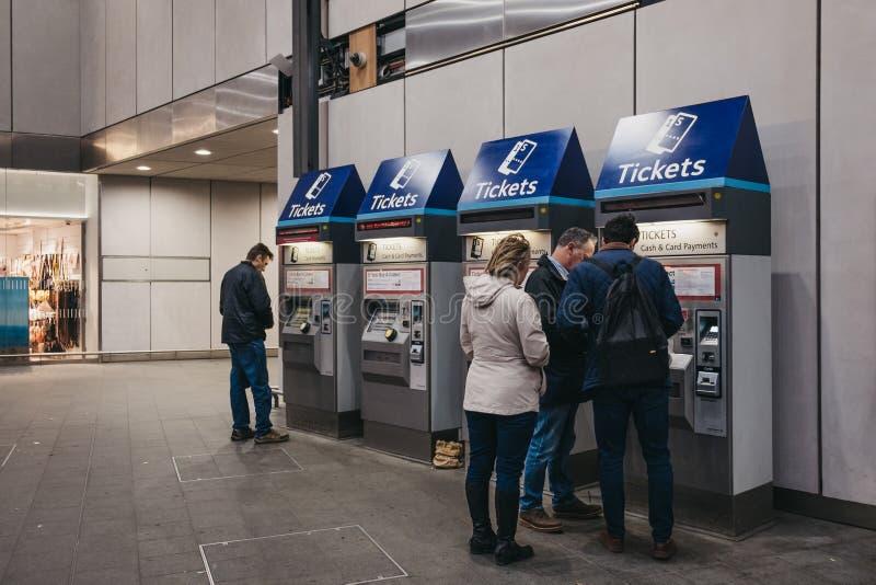 Boletos de la compra de la gente de una máquina del boleto dentro de la estación de tren del puente de Londres, Londres, Reino Un fotos de archivo libres de regalías
