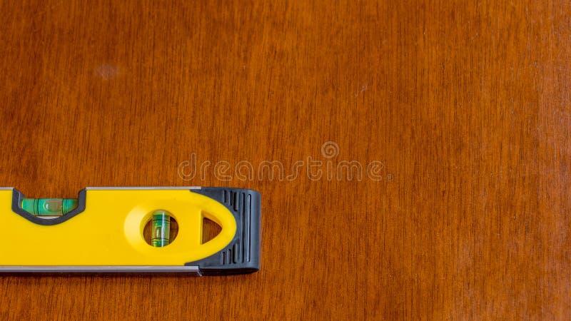 Bolha amarela da exibição do nível de bolha na posição nivelada para indicar um plano liso, descansando em uma superfície de made fotos de stock royalty free