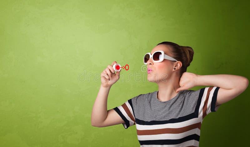 Bolha de sabão de sopro da mulher bonita no fundo do copyspace imagem de stock