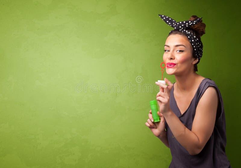 Bolha de sabão de sopro da mulher bonita no fundo do copyspace fotos de stock