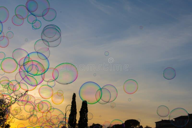 Bolhas de sabão coloridas contra o céu bonito do por do sol fotos de stock royalty free