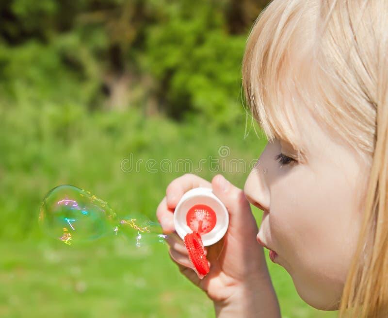 Bolhas de sabão de sopro da criança fotografia de stock royalty free