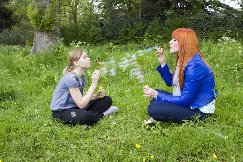 Bolhas de sabão de sopro da criança e da jovem mulher foto de stock