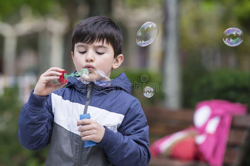 Bolhas de sabão de sopro da criança fora fotografia de stock royalty free