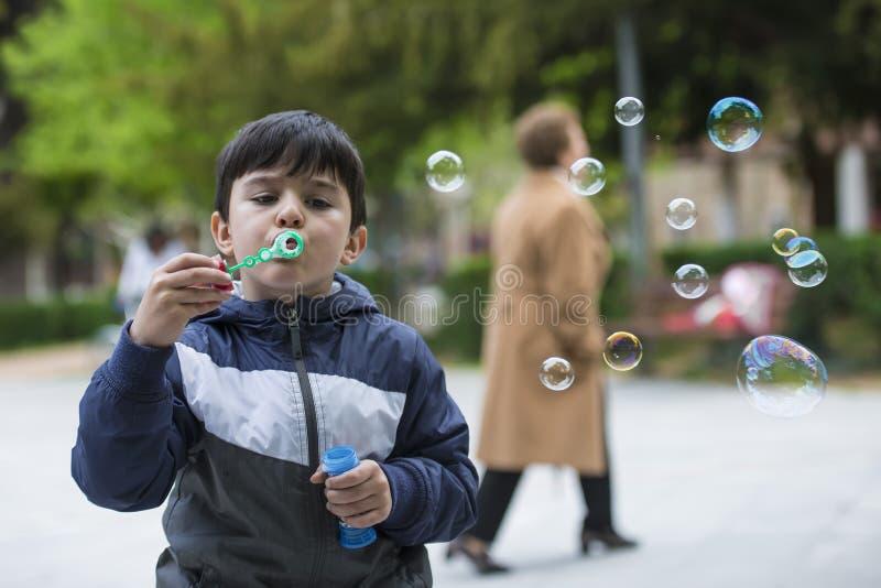 Bolhas de sabão de sopro da criança fora imagem de stock royalty free