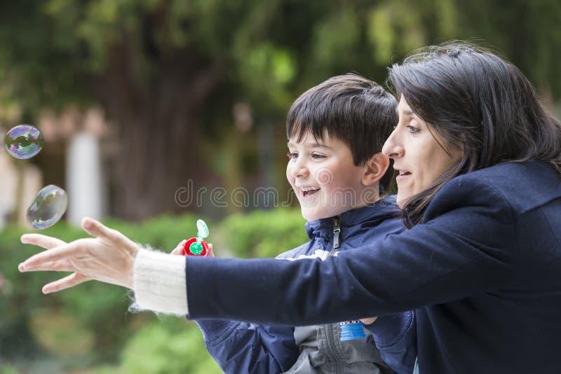 Bolhas de sabão de sopro da criança fora foto de stock royalty free