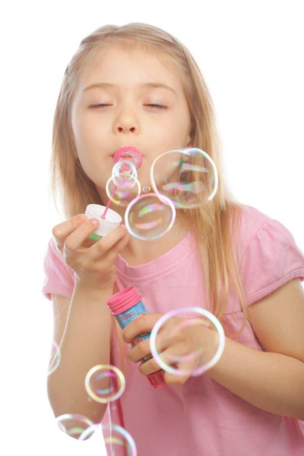 Bolhas de sabão de sopro da menina bonita engraçada imagens de stock