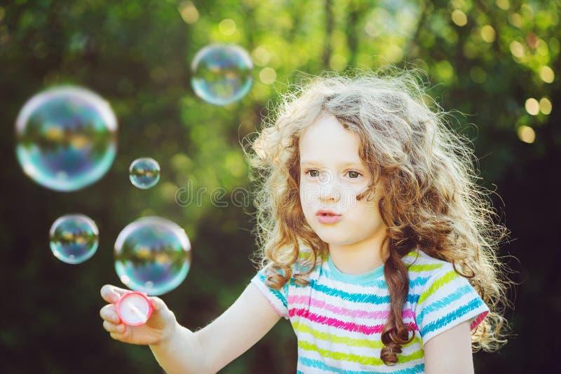 Bolhas de sabão de sopro da menina bonito, retrato do close up imagens de stock