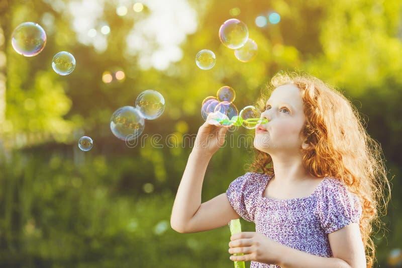 Bolhas de sabão de sopro da menina no parque do verão fotos de stock