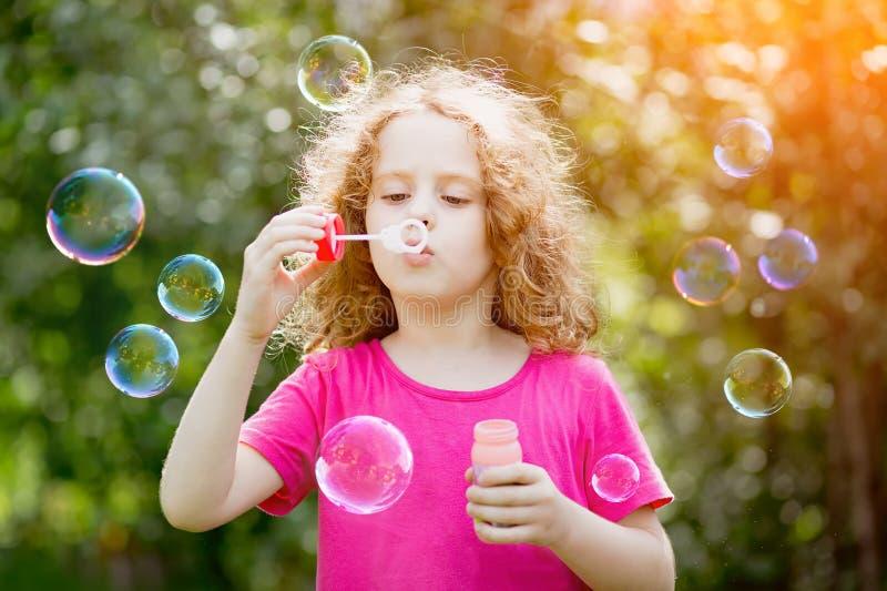 Bolhas de sabão de sopro da menina, tonificando para o filtro do instagram fotografia de stock royalty free