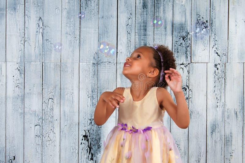 Bolhas de sabão de sopro de sorriso felizes da menina africana no fundo da parede de madeira imagem de stock