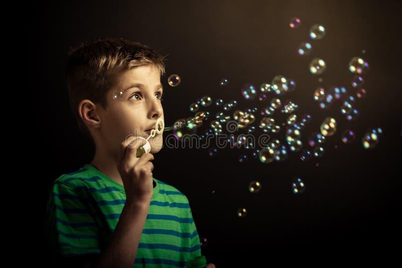 Bolhas de sabão de sopro do menino novo fotografia de stock