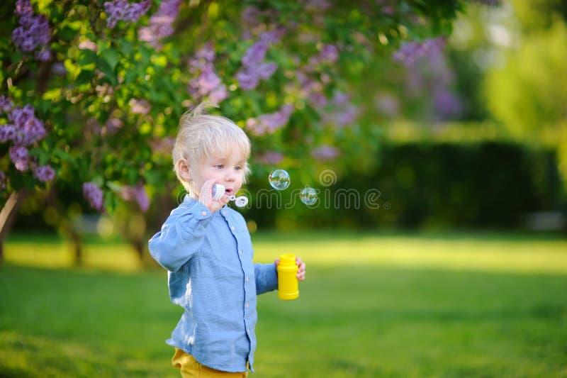 Bolhas de sabão de sopro do rapaz pequeno bonito no parque imagens de stock