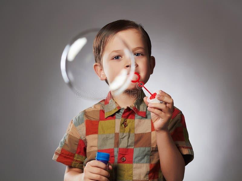 Bolhas de sabão de sopro do rapaz pequeno engraçado Criança feliz fotografia de stock