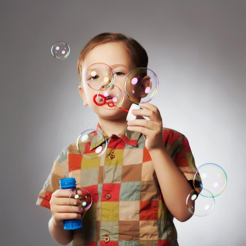 Bolhas de sabão de sopro do rapaz pequeno engraçado Criança feliz imagem de stock