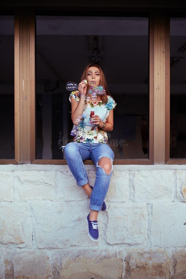 Bolhas de sabão de sopro do retrato da jovem mulher fotografia de stock