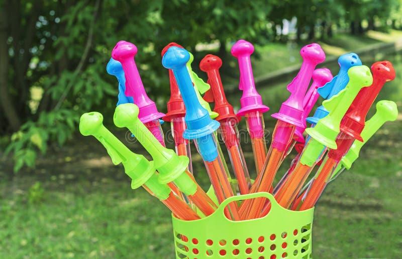 Bolhas de sabão do brinquedo na forma de um suporte da espada em uma cesta verde em um fundo natural imagens de stock royalty free