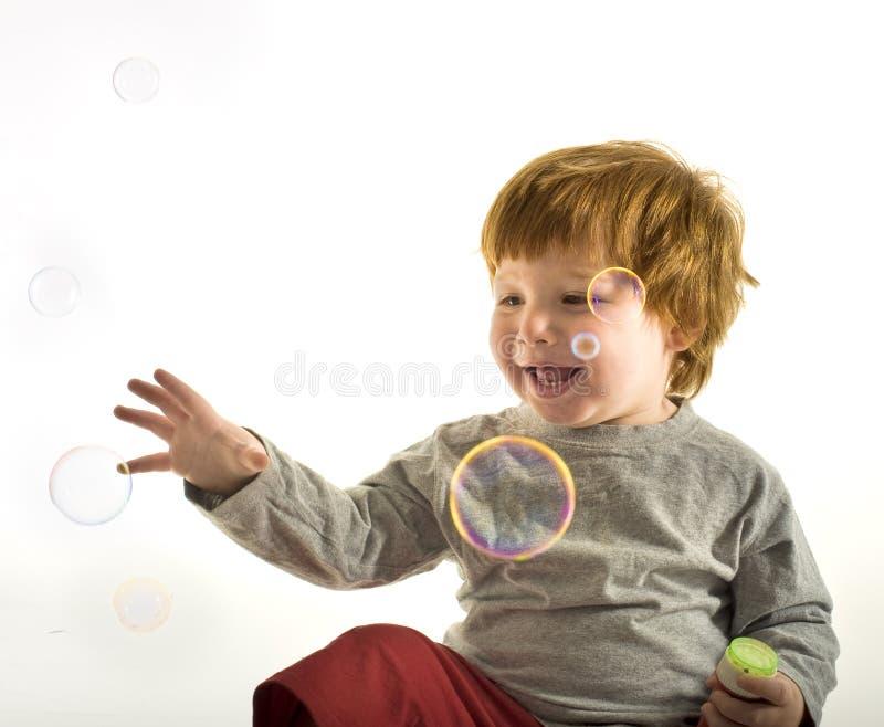 Bolhas de sabão do rapaz pequeno fotografia de stock