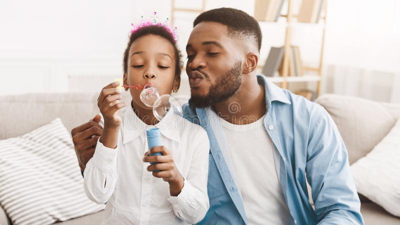 Bolhas de sabão felizes de And Daughter Blowing do pai em casa fotografia de stock royalty free