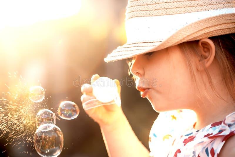 Bolhas de sabão de sopro da menina no parque do verão toned fotos de stock royalty free