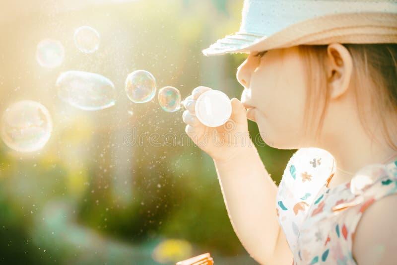 Bolhas de sabão de sopro da menina no parque do verão toned foto de stock